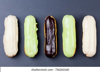 Eclairs, traditional french dessert. Slate background. Copy space. Top view.