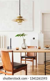 Eclectic and elegant dining room interior with design sharing table, chairs, gold pedant lamp, abstract paintings and stylish accessories. Tropical leafs in vase. Eclectic decor. Brown wooden parquet.