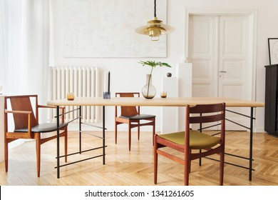 Eclectic and elegant dining room interior with design sharing table, chairs, gold pedant lamp, abstract paintings, piano and stylish accessories. Eclectic decor. Brown wooden parquet. Real photo.