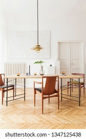 Eclectic and elegant dining room interior with design sharing table, chairs, gold pedant lamp, abstract paintings and stylish accessories.Tropical leafs in vase. Minimalistic decor. Real photo.