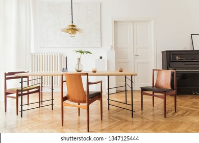 Eclectic and elegant dining room interior with design sharing table, chairs, gold pedant lamp, abstract paintings, piano and stylish accessories. Minimalistic decor. Brown wooden parquet. Real photo.