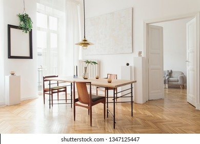 Eclectic and elegant dining room interior with design sharing table, chairs, gold pedant lamp, abstract paintings and stylish accessories. View to living room. Eclectic decor. Brown wooden parquet.
