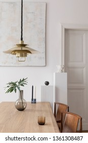 Eclectic and elegant dining room interior with design sharing table, chairs, gold pendant lamp, abstract paintings and stylish accessories. Tropical leafs in vase.Eclectic decor. Brown wooden parquet.