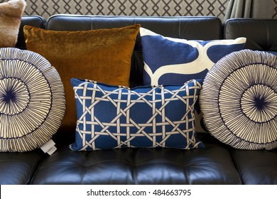 Eclectic pillows setting on a black sofa