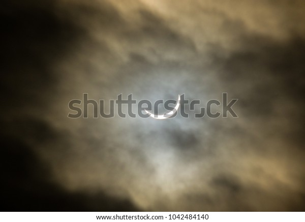 the eclipse in England through a cloudy sky