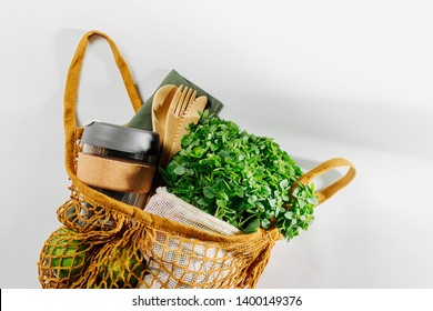 Eco bag with Eco friendly bamboo cutlery, reusable coffee mug and fresh green. Sustainable lifestyle. Plastic free concept. Flat lay, top view