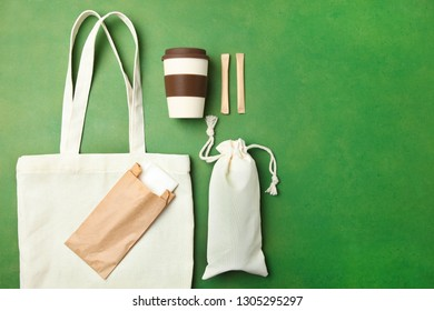 Eco bag, reusable bamboo cup and craft packages on green background. Concept ecology conservation. Flat lay, copy space. Environmentally friendly materials.