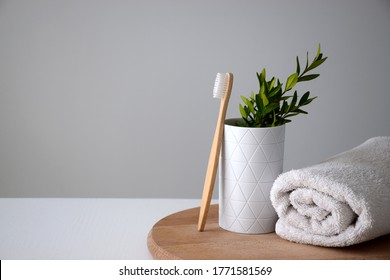 Eco bamboo tooth brush near white holder and white rolled towel on wooden round board. Dental treatment or oral cavity care concept. Copy space.