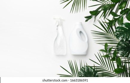 Eco cleaning detergent in white plastic bottles with green leaves on white background, copy space. Eco recycling cleaning product