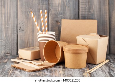 Eco craft paper tableware. Paper cups, dishes, bag, fast food containers and  wooden cutlery on wooden background. Recycling concept. Copy space