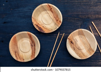 Eco, environment friendly disposable plate made from bamboo on dark wooden rustic background with chopsticks, top view, overhead