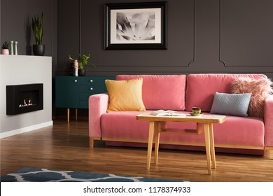Eco fireplace in real photo of dark living room interior with poster on wall with wainscoting, wooden coffee table and powder pink lounge