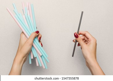 Eco friendly alternative to plastic drink cans. In one hand the girl has a lot of plastic pink and blue tubes. In other hand holds a reusable metal tube. Choice between plastic vs steel. Top view