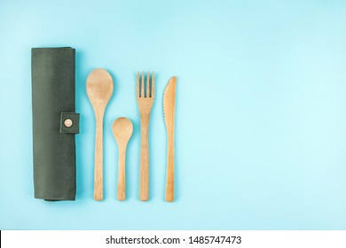 Eco friendly bamboo cutlery set on blue background. Zero waste concept.