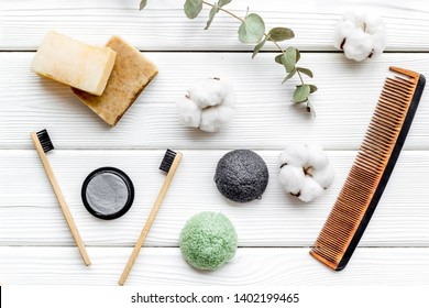 eco friendly bamboo tooth brush and carbon toothpaste, comb, organic soap on white background top view