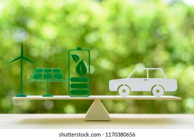 Eco friendly car / green renewable energy, save earth and nature concept : Windmill or wind turbine, solar energy panel, dried cell battery and leaf, white sedan car on a seesaw / simple balance scale