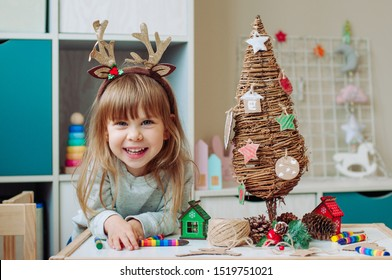 Eco friendly Christmas tree concept. Happy little toddler 3-years old girl sitting at the table near wooden Christmas tree with handmade corrugated cardboard decorations. Selective focus.