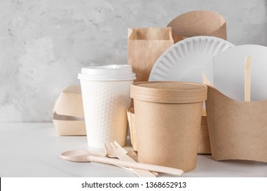 eco friendly disposable dishes made of bamboo wood and paper on white marble background. Draped spoons, fork, knives, plate with paper cups. recycling concept