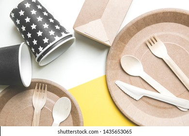 eco friendly disposable dishes made paper on white marble background. Draped spoons, fork, knives, plate with paper cups. recycling concept