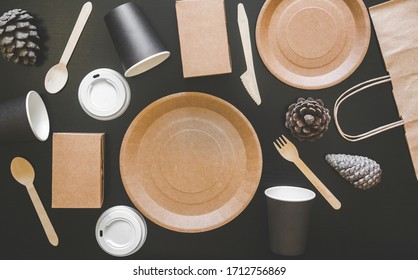 eco friendly disposable dishes made paper on black background. Draped spoons, fork, knives, plate with paper cups. recycling concept