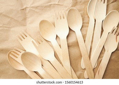 eco friendly disposable kitchenware utensils on paper background. look from above. wooden forks and spoons. eco friendly concept.