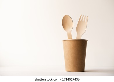eco friendly disposable kitchenware utensils on white background. wooden forks and spoons in paper cup. ecology, zero waste concept. copyspace.