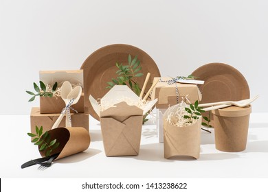 Eco friendly, disposable, recyclable, compostable tableware. Paper food boxes, dishes and flower pots with saw shawings and rowan branches in them and cornstarch cutlery over white background