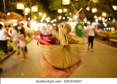 A eco friendly juice container made from Nipa or mangrove palm leaf is full with traditional sweet palm juice and ice. Decorated with purple orchid with Thai traditional night market as background