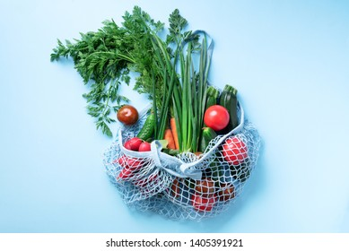 Eco friendly mesh bag with organic green vegetables on blue background. Flat lay, top view. Zero waste, plastic free concept. Healthy clean eating diet and detox