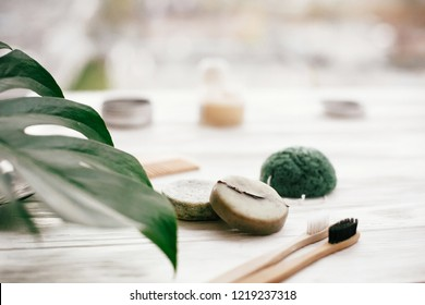 Eco friendly natural bamboo toothbrushes, shampoo bar, toothpaste in glass, wooden brush and konjaku sponge on white wood with green monstera leaves. Zero waste concept, plastic free