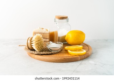 Eco friendly natural cleaners, jar with baking soda, dish brush, lemon, soap on white marble table background. Organic ingredients for homemade cleaning. Zero waste concept.