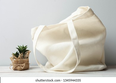 Eco friendly reusable recyclable white eco bag and succulent on gray background. Concept zero waste.