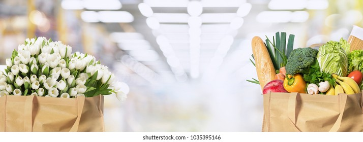 Eco friendly reusable shopping bags filled with vegetables and flowers on a supermarket blured background
