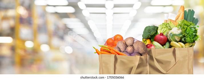 Öko-freundliche wiederverwendbare Einkaufstaschen mit Brot, Obst und Gemüse auf Supermarkthintergrund