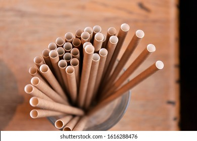 Eco friendly Reusable Straws in the cardboard cup with selective focus and blurred ba. Paper cocktail tubes. Kraft paper straw for drinking coffee or tea. Disposable cocktail tube.