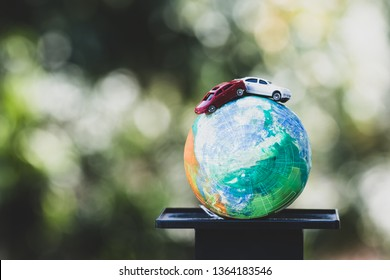 Eco friendly Save world concept. Red car on Model globe clay with radar scales balance on Natural background. Ideas of earth maintenance by reducing energy consumption, Travel around world
