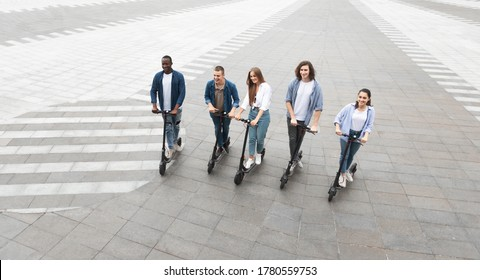 Eco Friendly Transport. Five cheerful smiling multicultural friends riding e-scooters, high angle view