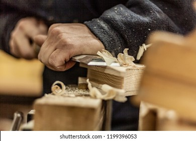 Eco friendly woodworker's shop. Details and focus on the texture of the material, saw dust, and planers or chisels, while making legs for a designer coffee table. Mastering wood with peacefullness.
