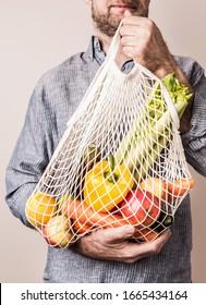 Umweltfreundliches (Null-Abfall-)Lebensstil und gesundes Ernährungskonzept. Mann, der wieder verwendbare Mesh-Einkaufstasche mit frischem Obst und Gemüse hält - Nahaufnahme.