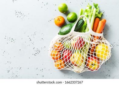 Umweltfreundliches Einkaufen und gesundes Lifestyle-Konzept. Baumwollmaschen-Beutel mit frischen bunten Früchten und Gemüse auf grauem Hintergrund. Von oben aufgezeichnet (Draufsicht, flache Lage) - Kopienraum.