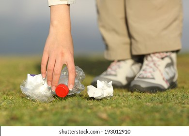 Eco hiker hand collecting garbage in the grass of the mountain