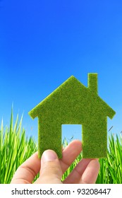 Eco house concept ,hand holding eco house icon in nature background