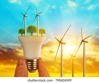 Eco LED bulb with wind turbines in hand at sunset. The concept of money saving and alternative energy.