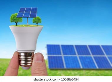 Eco LED light bulb with solar panels in hand. Concept of green energy.
