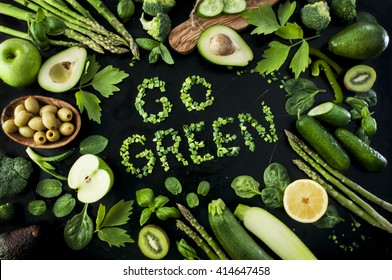Eco living. Go green background. Variety of green vegetables, herbs and fruits on the black table. Natural lettering made of chive. Green and black poster.