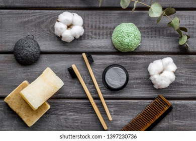 Eco materials concept with bamboo tooth brush and toothpaste with bamboo carbon on wooden background top view