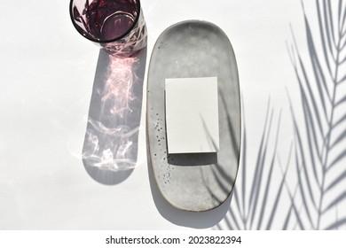 Eco minimal tableware scene.  Empty blank on ceramic plate, cocktail glass on neutral background. Sunlight, palm shadow.  Mockup invitation card for wedding, business or menu. Wabi sabi style