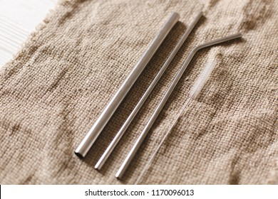 eco natural metallic straws flat lay on  rustic background. sustainable lifestyle concept. zero waste, plastic free items. stop plastic polution. reuse, reduce, recycle, refuse