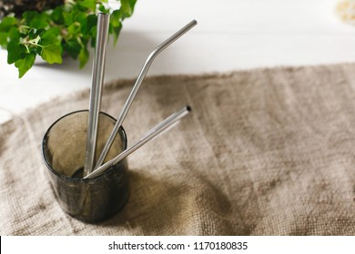 eco natural metallic straws in green glass on rustic background with greenery. sustainable lifestyle concept. zero waste, plastic free items. stop plastic pollution.