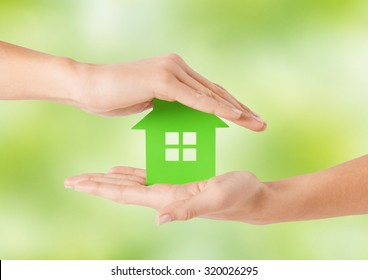 eco, people and real estate concept - close up of woman hands holding green house over natural background